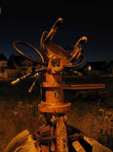 Anschlussstück und -schläuche einer Baggerschaufel des Nachts